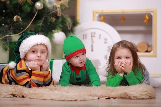 그의 오 빠와 여동생 산타 모자 선물 상자 크리스마스 트리 아래에 앉아 빨간색 녹색 요정 의상에서 아기 소년.