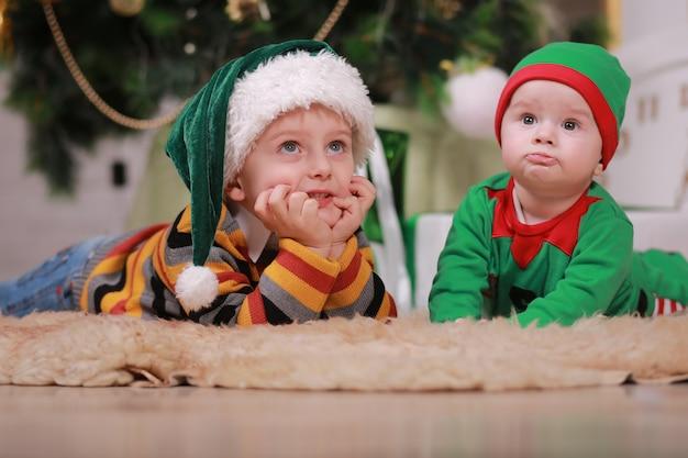 크리스마스 트리와 선물 상자 아래에 앉아 산타 모자에 그의 형과 함께 빨간색 녹색 요정 의상 아기 소년.