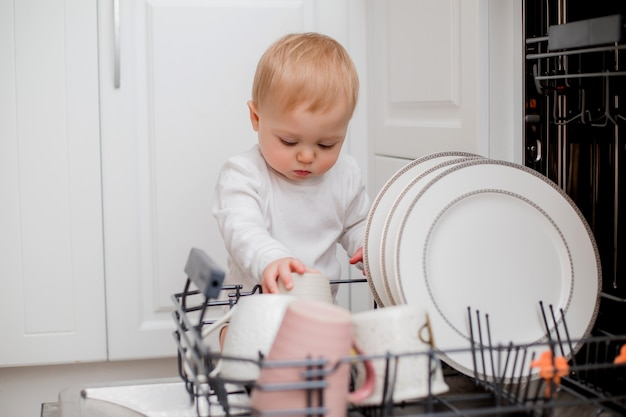 白い服を着た男の子は食器洗い機を使用しています