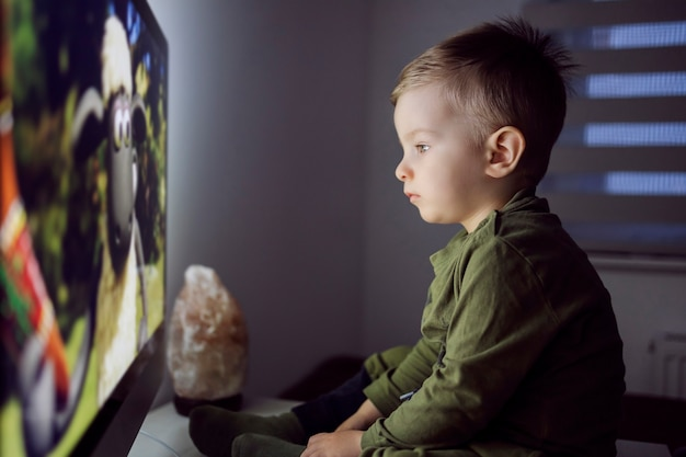 A baby boy is sitting right in front of the tv and staring at a cartoon movie