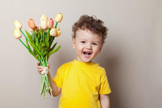 Baby boy laughing among pink tulips