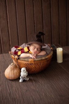 Baby boy laying inside little basket with funny wizard costume