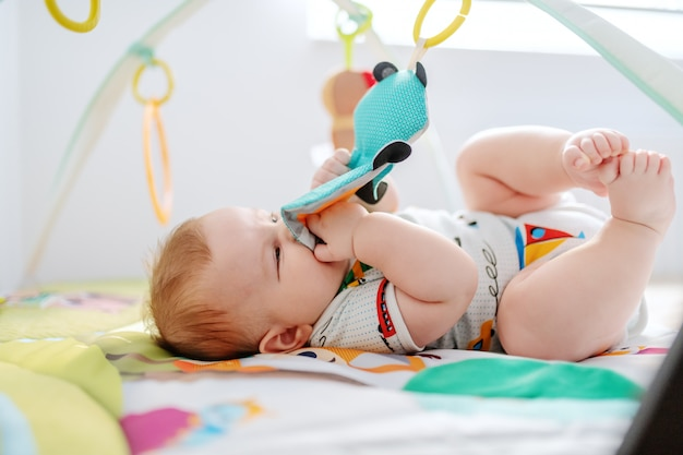 Baby boy lying in and playing with crib toys.