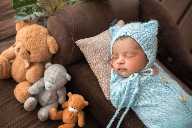 3つのおもちゃのクマに囲まれた茶色のソファの上の青いかぎ針編みのピジャマで寝ている生まれたばかりの赤ちゃん