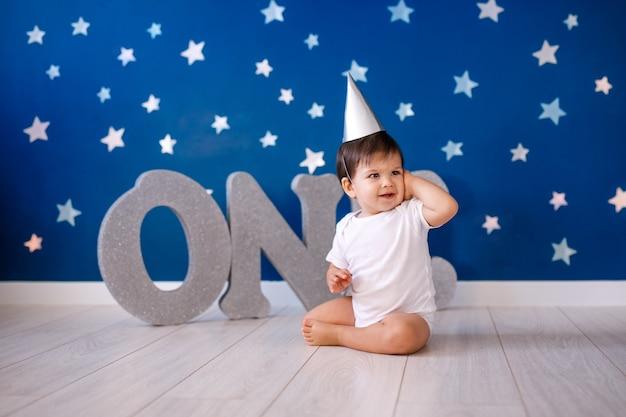 Годовалый мальчик в белом теле и праздничной бумажной шляпе сидит на полу на синей стене со звездами и большими серебряными буквами one.