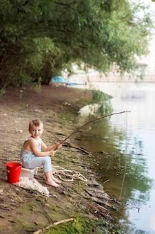 釣り竿を持って川の近くの砂浜で男の子の赤ちゃん