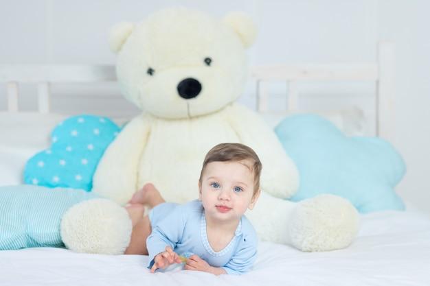 파란색 바디수트를 입은 큰 테디베어와 함께 침대에 있는 아기, 침실에서 행복한 건강한 작은 아기