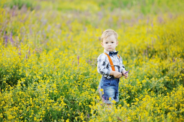 Baby boy in orange suspenders and bow tie on a background field of flowers