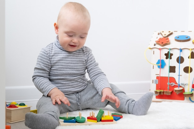 바쁜 보드와 나무 장난감에서 노는 아기. 초기 아동 발달.