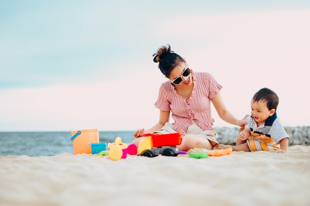 Baby boy playing with beach toys with his mother on tropical beach.