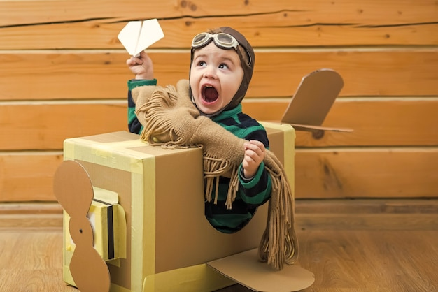 Baby boy playing with cardboard airplane on wooden room