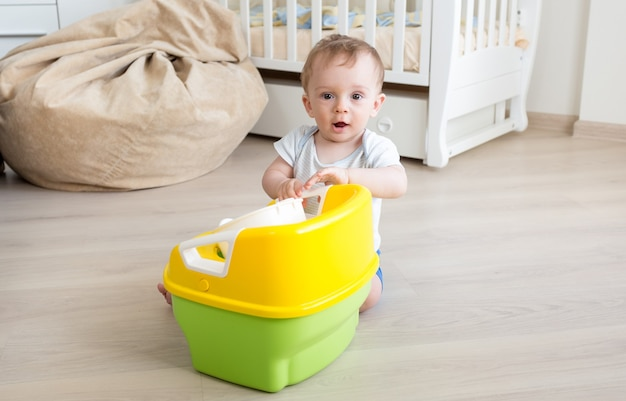 Baby boy playing with chamber pot on floor at living room