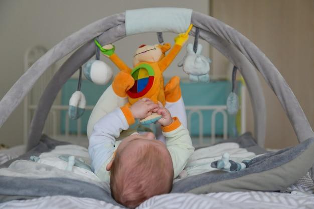 개발 매트에 매달려 장난감을 가지고 노는 아기