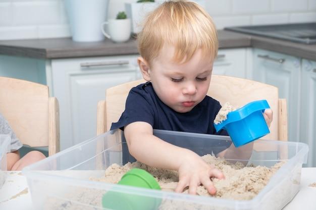 家でキネティックサンドで遊ぶ男の子。幼い頃の教育。幼児が遊んでいます。