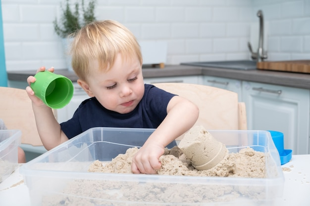 Baby boy playing with kinetic sand at home