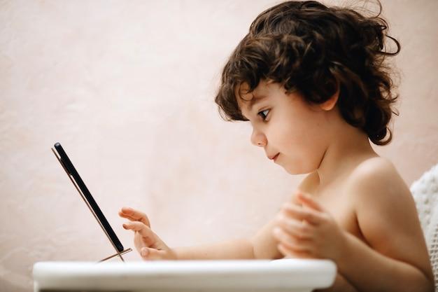 携帯電話で遊ぶ男の子の赤ちゃん。子供の手の中に新しいデジタル技術。スマートフォンを持つ幼児の肖像画