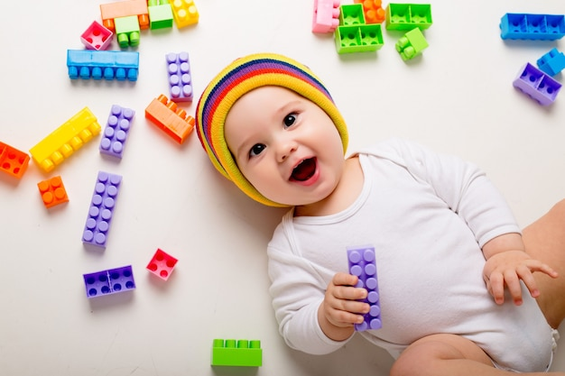 Baby boy playing with a multi-colored constructor on a white wall