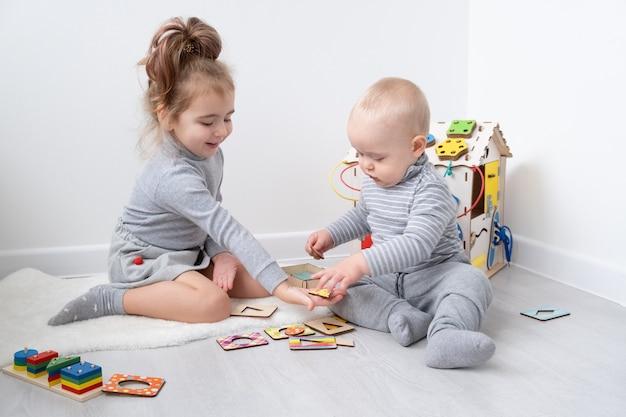 나무 장난감으로 누나와 노는 아기 소년. 초기 아동 발달.