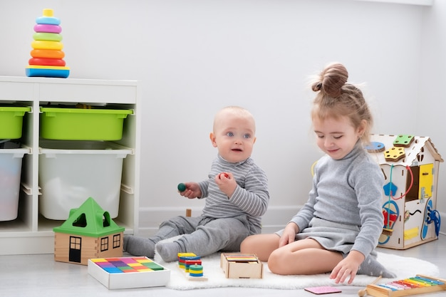 Мальчик играет со старшей сестрой с деревянными игрушками. раннее развитие детей.