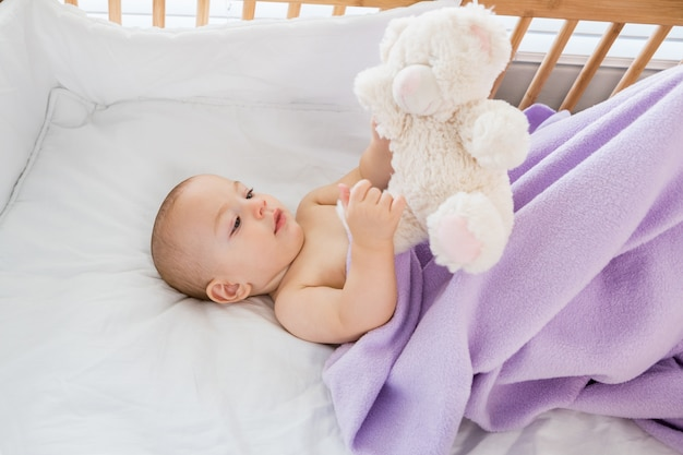 Baby boy playing with a soft toy on a cradle