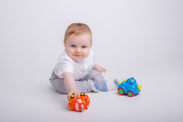 Baby  boy playing with toy cars on white background