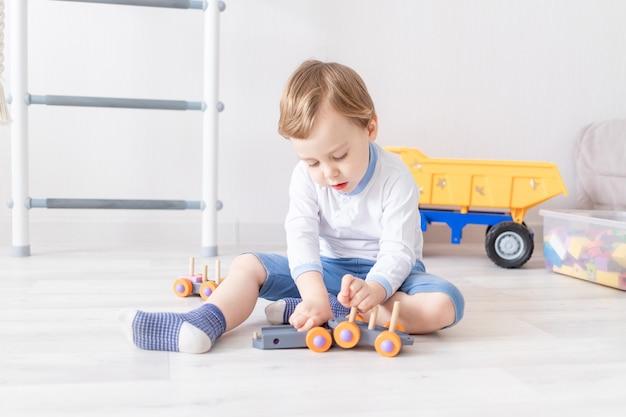 바닥에 집에서 나무 장난감을 가지고 노는 아기