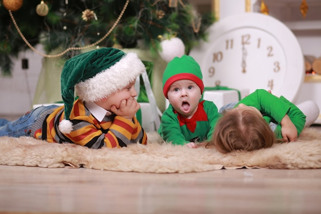Baby boy in red green elf costume with his older brother and sister in santa hats sitting under christmas tree with gift boxes.