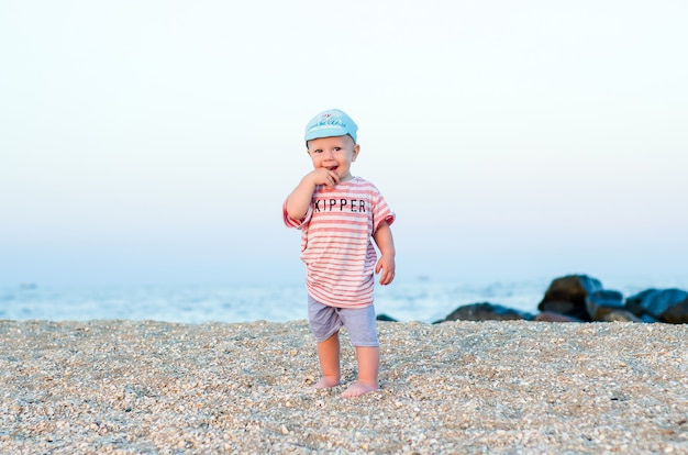 Baby boy on the sand near sea in blue hat and striped clothes. summer concept. holiday relaxing, beach vacation.