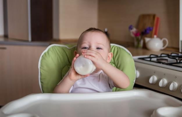 아기는 의자에 앉아 병에서 음료
