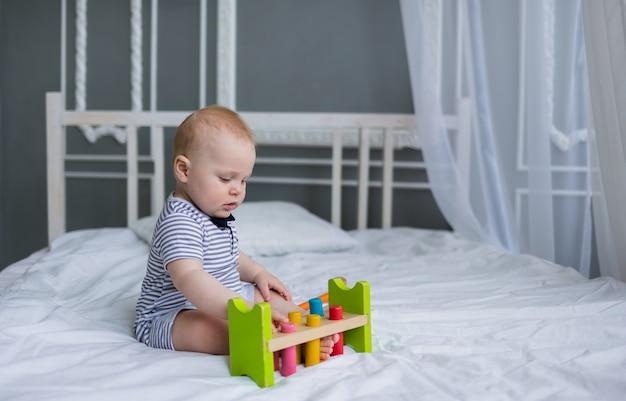 아기는 줄무늬 점프 슈트에 앉아 방에있는 흰색 침대에 나무 장난감을 가지고 노는