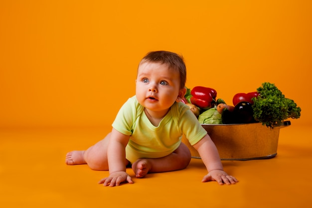 Baby boy sits next to the pelvis with fresh vegetables. concept of eco-friendly farm products