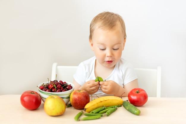 Мальчик сидит за столом и ест фрукты и овощи