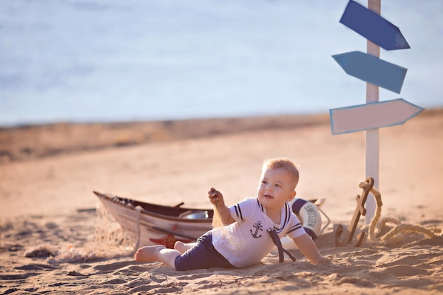Baby boy sitting in a boat, dressed as a sailor, on a sandy beach with seashells by the sea