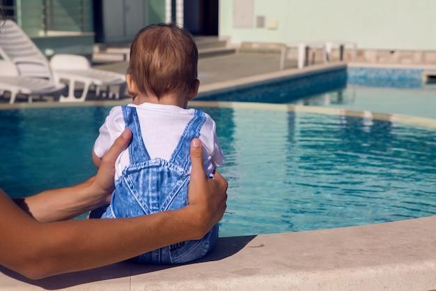 デニムのスーツを着てプールのそばに座っている男の子