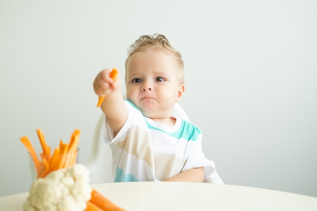 Baby boy sitting in a childs chair eating carrot slices on white background