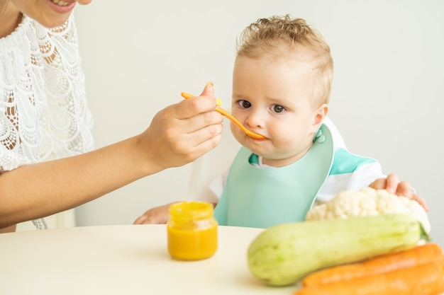 Baby boy sitting in a childs chair eating vegetable puree on white kitchen. mom feeds baby.