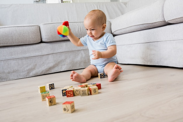 Baby boy sitting on floor and playing with toys in living room