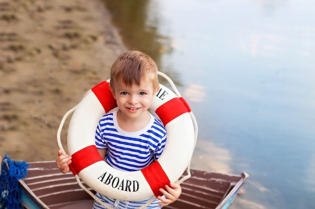海沿いの貝殻の砂浜で、船乗りに扮したボートに座っている男の子