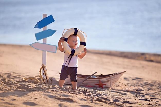海沿いの貝殻を持つ砂浜のビーチで船乗りに扮した男の子の赤ちゃん