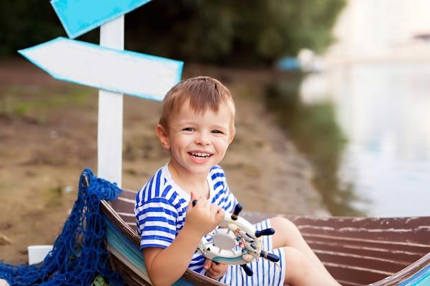 Мальчик сидит в лодке на пляже