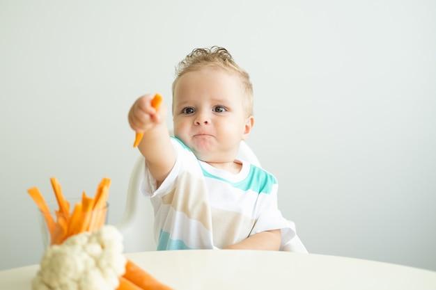 Мальчик сидит в детском кресле и ест морковь на белом фоне