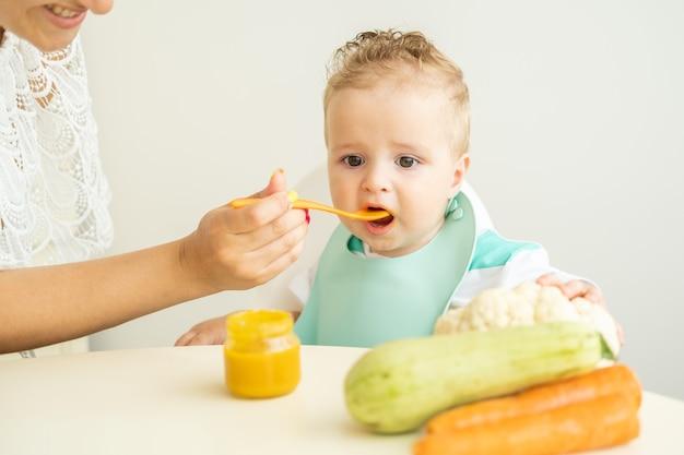 흰색 부엌 엄마가 아기에게 먹이를 주는 야채 퓌레를 먹는 차일드 의자에 앉아 있는 아기