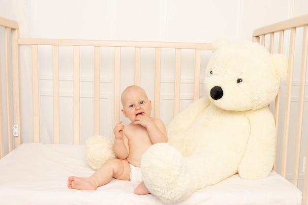 Мальчик сидит в подгузниках в кроватке с большим плюшевым мишкой в детской