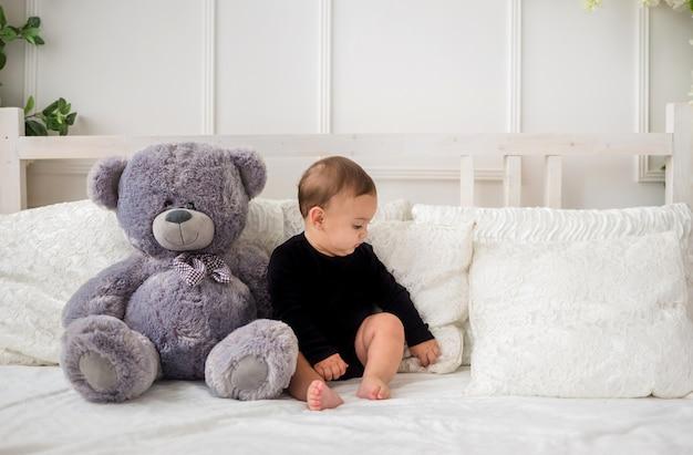大きな灰色のテディベアと黒のボディースーツでベッドに座っている男の子