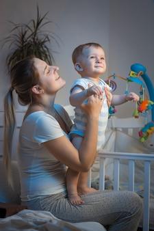 夜、寝室で母親の膝の上に座っている男の子