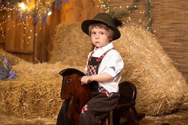 レトロな衣装を着ておもちゃの馬に座っている男の子