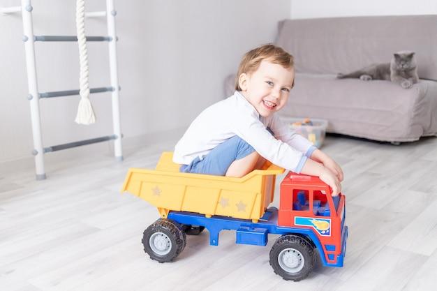 子供のゲームの概念自宅でタイプライターに座ったり乗ったりする男の子