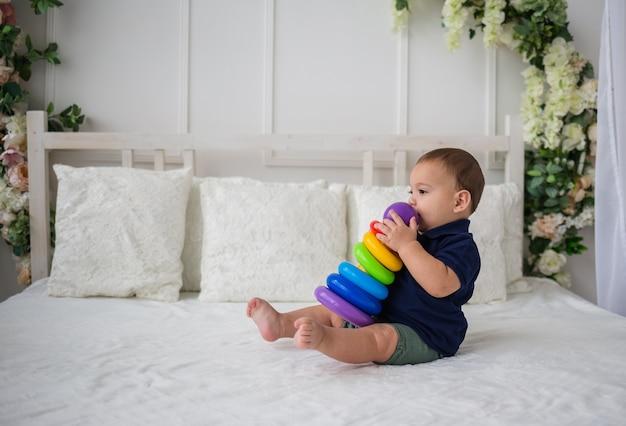 Мальчик сидит боком на кровати и играет с игрушкой-пирамидкой