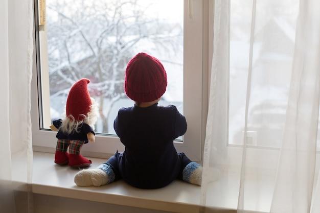 Мальчик сидит с мягкой игрушкой гном на окне