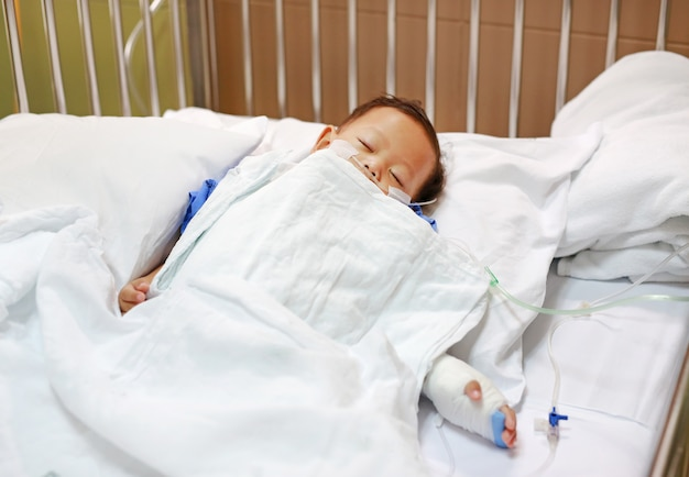 Baby boy sleeping with attaching intravenous tube to hand on bed at hospital.